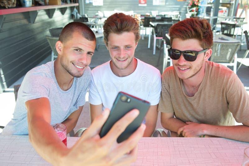 采取在餐馆酒吧的朋友selfie户外 库存图片
