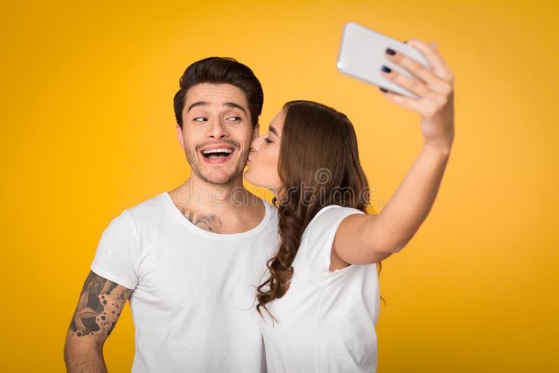 采取在黄色背景的可爱的夫妇selfie 免版税库存图片
