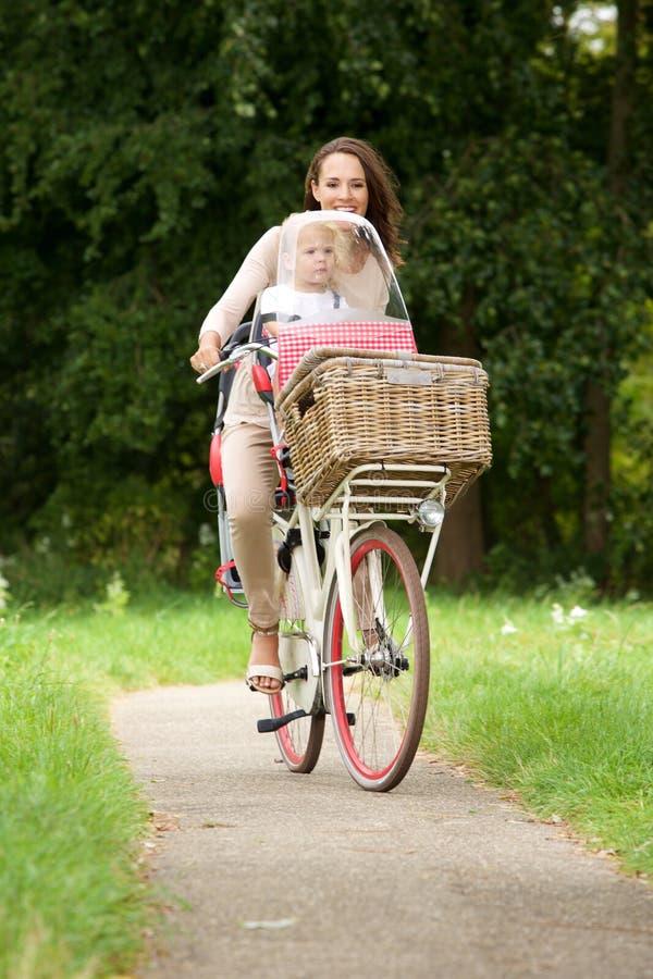 采取她的自行车乘驾的妇女小女儿 免版税库存照片