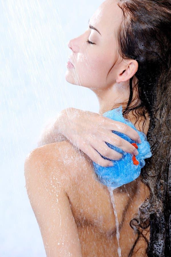 采取妇女年轻人的美丽的bodycare阵雨 免版税库存照片