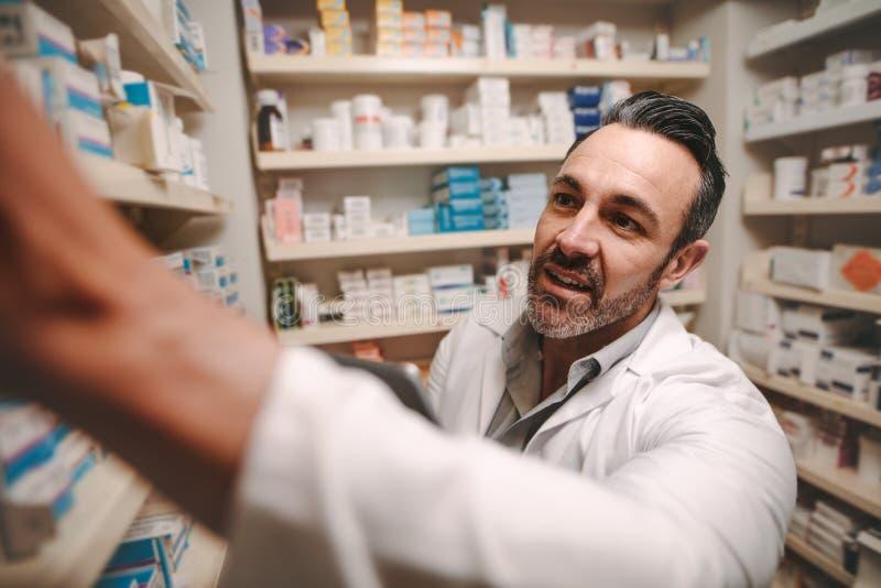 采取存货的男性化学家在药房商店 免版税图库摄影