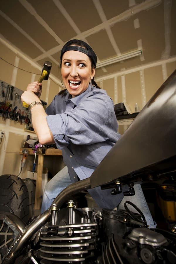 采取对妇女的摩托车sledghammer 库存照片
