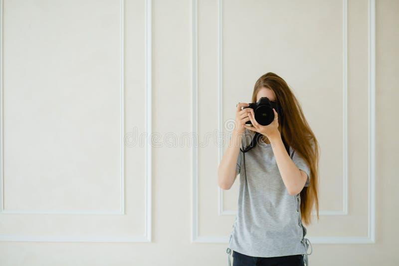 采取射击的妇女摄影师在演播室 免版税图库摄影