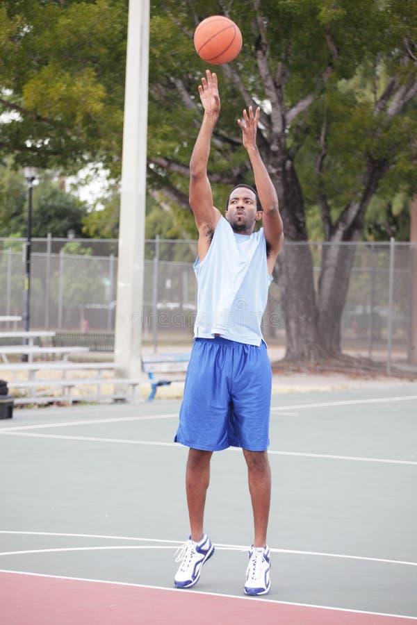 采取射击的蓝球运动员 免版税库存照片