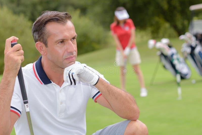 采取射击的被集中的高尔夫球运动员在高尔夫球场 免版税库存照片