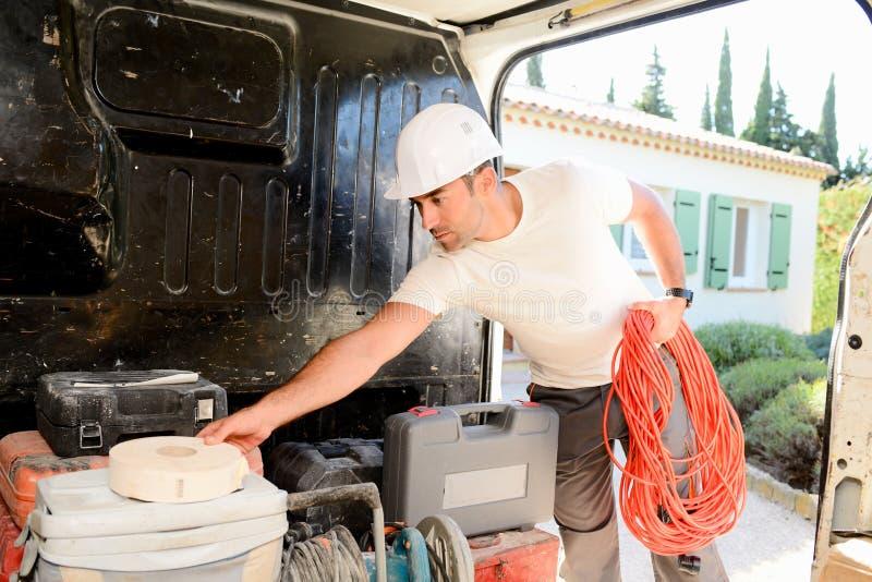 采取工具的年轻电工工匠在专业卡车搬运车外面 免版税图库摄影