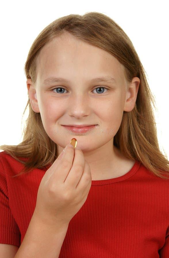 采取年轻人的女孩药片 免版税库存照片