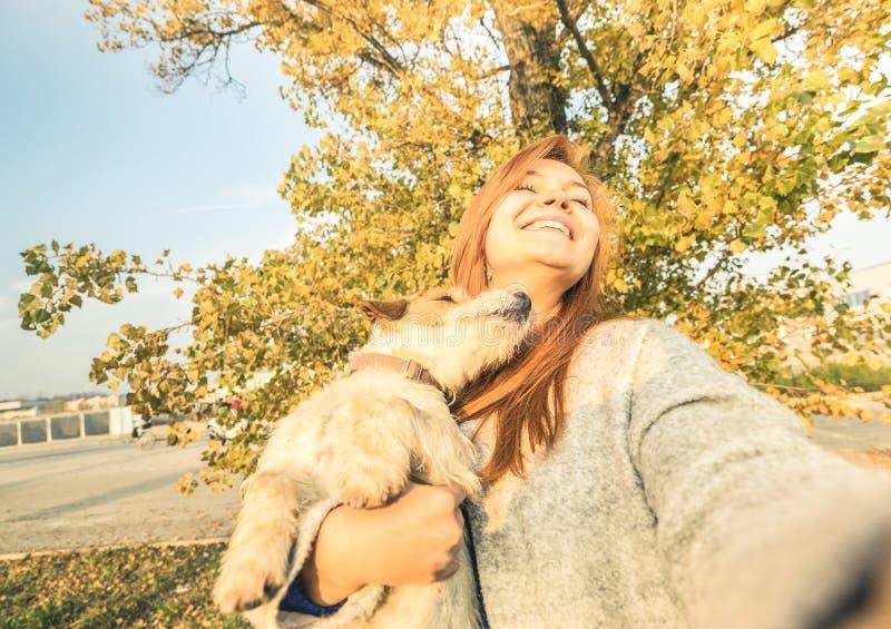 采取惊奇的selfie的年轻红头发人妇女户外与狗 免版税库存图片
