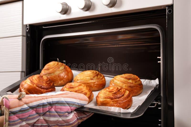 采取新近地被烘烤的小圆面包的妇女在烤箱外面 库存图片