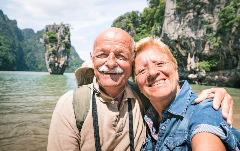 采取旅行selfie的愉快的退休的资深夫妇在世界范围内- 免版税库存图片