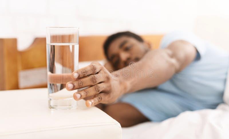 采取杯水的年轻人在床上 库存图片