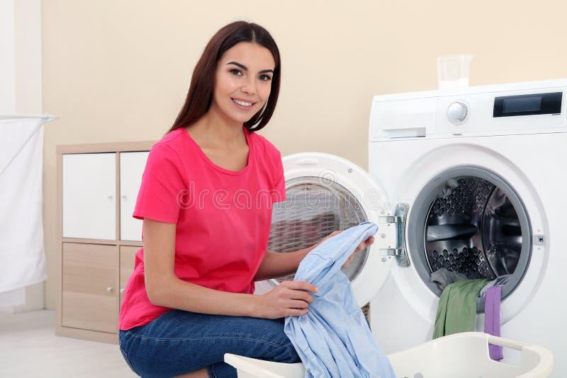 采取洗衣店的年轻女人在洗衣机外面 库存照片