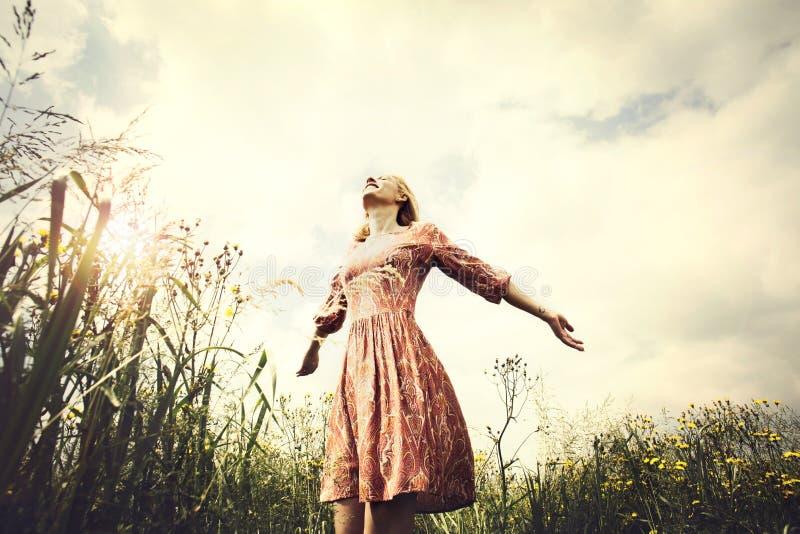 采取深呼吸的美丽的妇女在日落 图库摄影