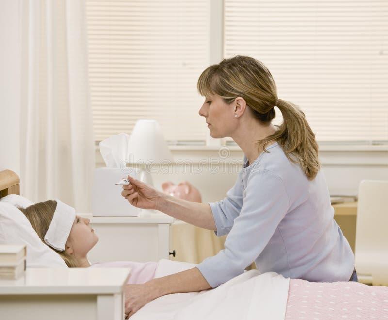采取温度的女儿不适的母亲s 免版税库存照片