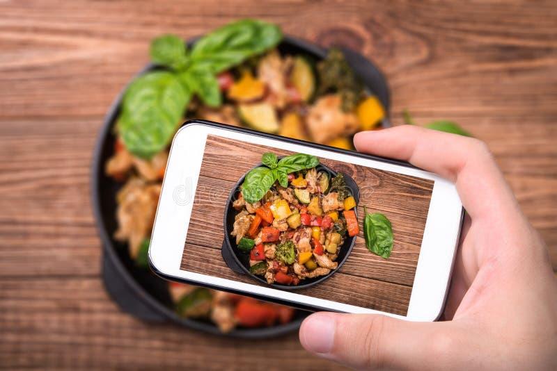 采取照片墨西哥鸡混乱的手油煎与智能手机 图库摄影
