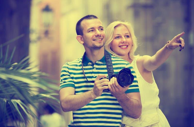 采取照相机的愉快的男人和妇女游人 免版税库存图片