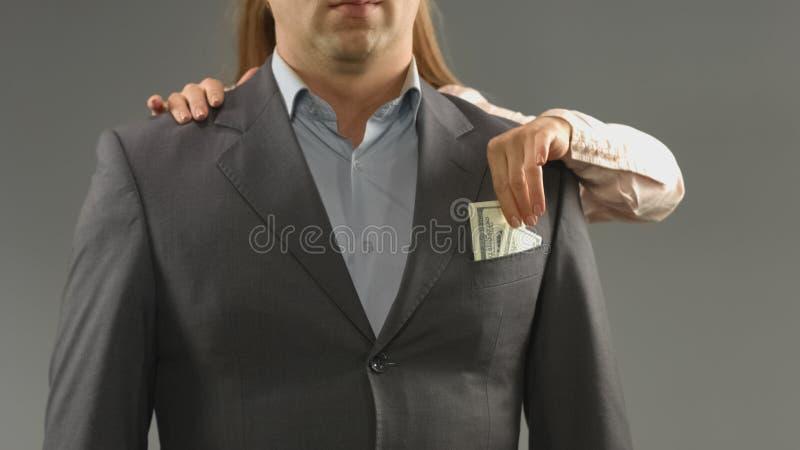采取现金金钱从的狡猾女朋友人口袋,婚约,欺骗 库存照片