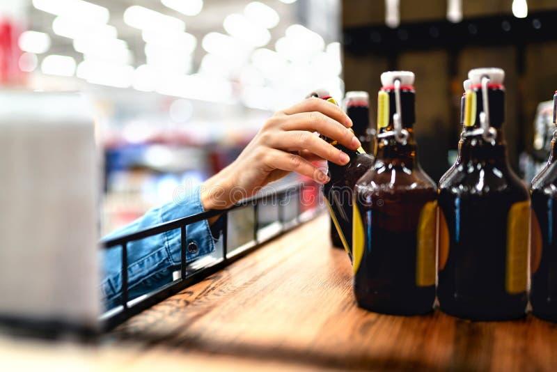 采取瓶从架子的啤酒的顾客在酒店 妇女购物的酒精或超级市场职员装填和长袜 免版税库存照片
