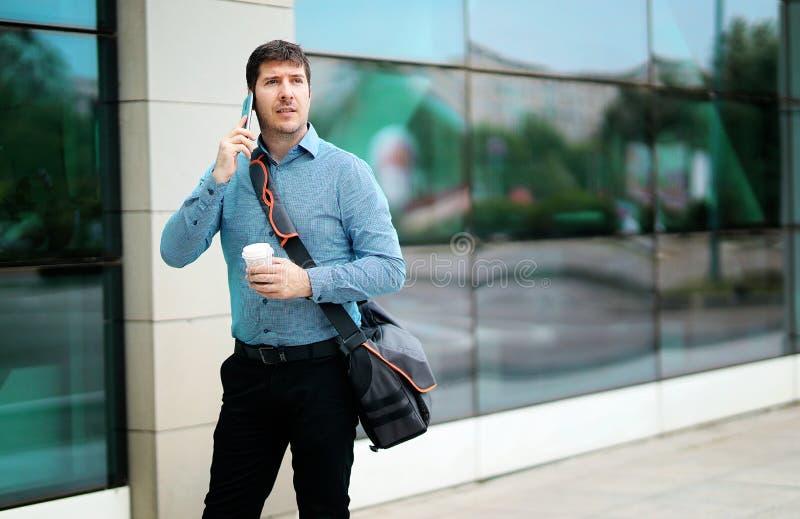 采取电话的射击一个英俊的通勤者,当走在办公楼之外时 库存图片