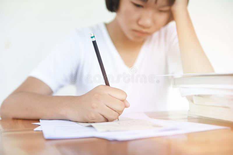 采取笔记和使用铅笔的类的检查重音/教育年轻女性学院坐学会概念注重了学生 图库摄影