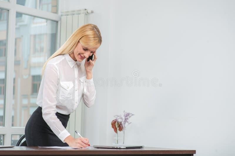 采取笔记和talkin的成功的女实业家或企业家 库存照片