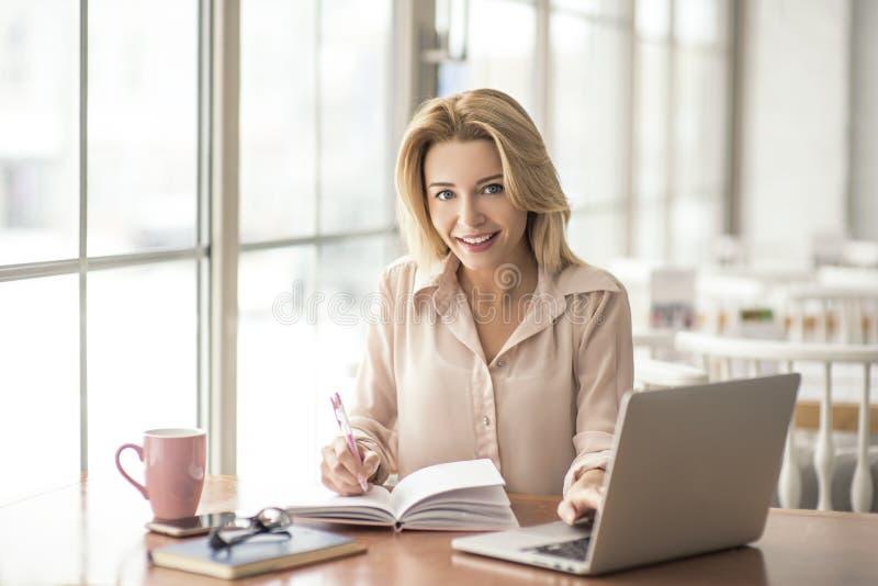 采取笔记的咖啡馆坐的浏览膝上型计算机的少妇看好奇的照相机 库存照片