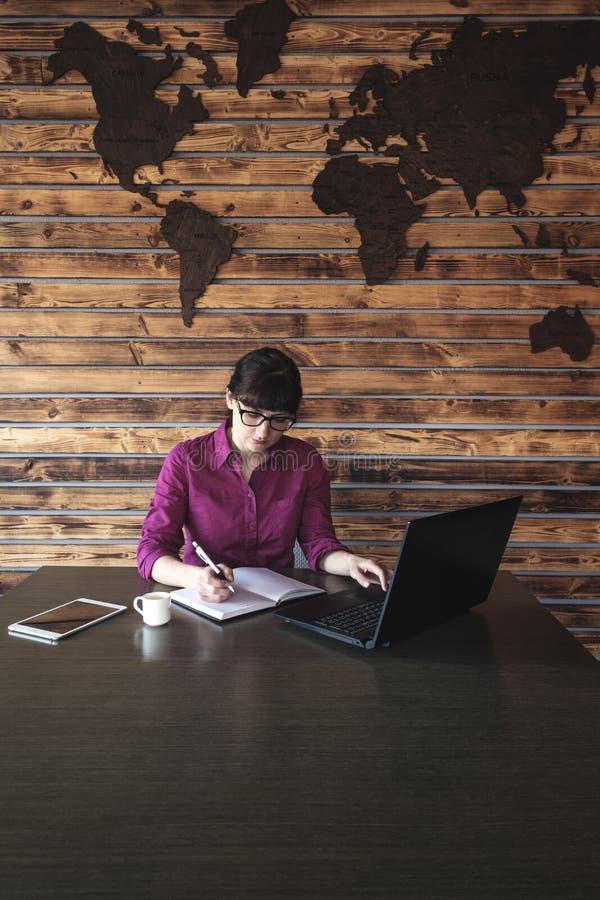 采取笔记的女实业家,她工作 免版税库存图片