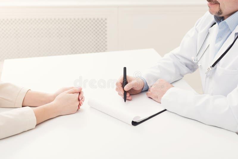 采取笔记的患者和医生特写镜头  免版税库存照片