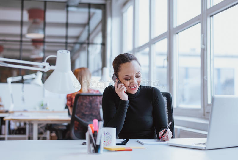采取笔记的愉快的少妇,当谈话在手机时 免版税库存图片