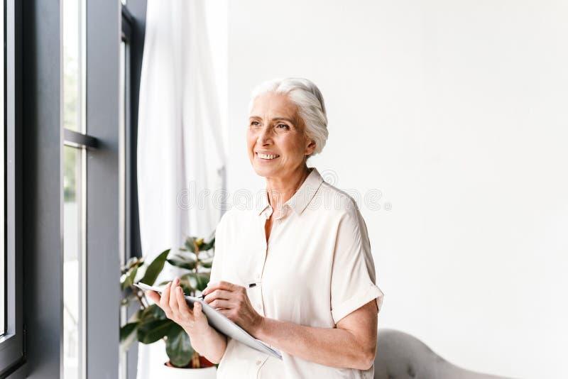 采取笔记的愉快的成熟的商业妇女 库存照片