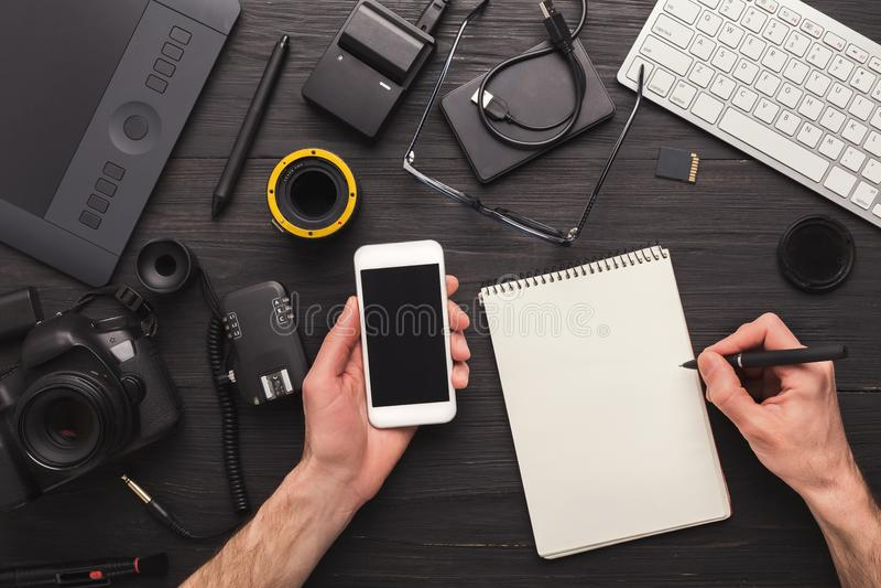 采取笔记的摄影师,当使用智能手机时 图库摄影