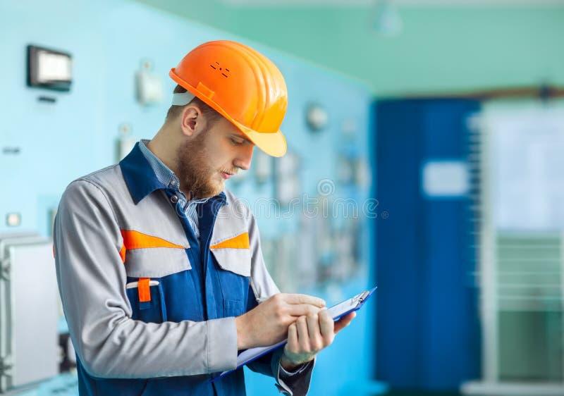 采取笔记的年轻工程师画象在控制室 库存图片