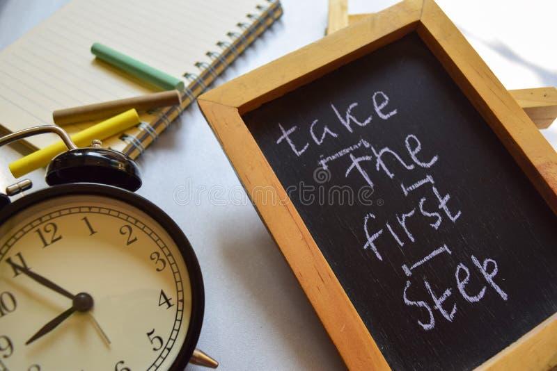 采取第一步词组五颜六色手写在黑板、闹钟以刺激和教育概念 免版税库存图片
