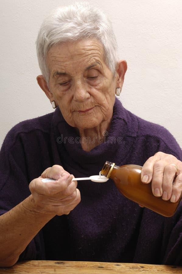 采取糖浆的资深妇女 免版税库存图片