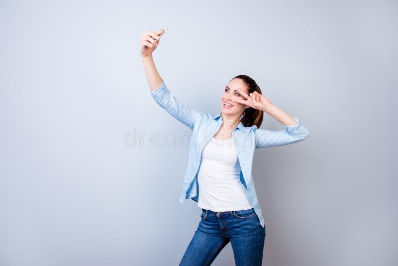 采取自已portr的衬衣和牛仔裤的愉快的激动的微笑的妇女 免版税图库摄影
