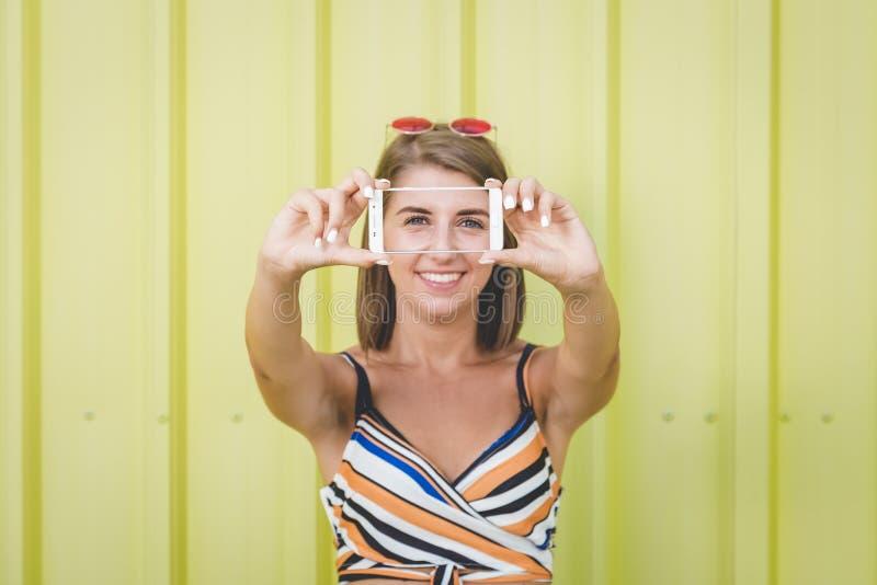 采取自画象的行家女孩通过使用手机对黄色墙壁 库存图片