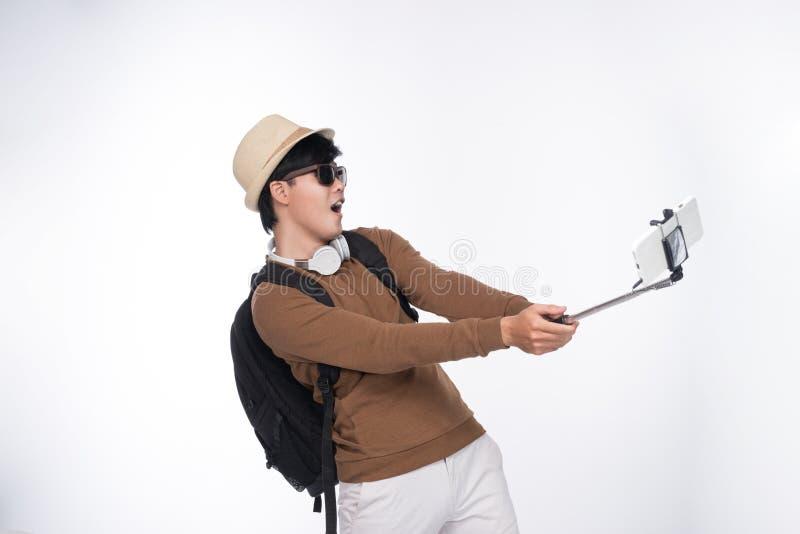 采取自画象摄影的愉快的年轻亚裔人通过s 图库摄影