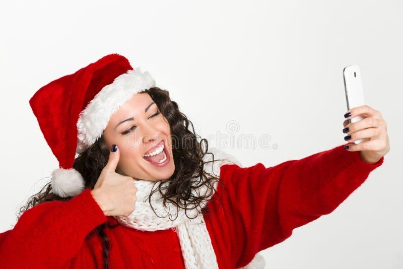 采取自画象的可爱的浅黑肤色的男人圣诞老人女孩 免版税库存照片