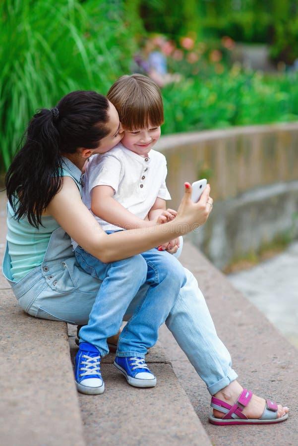 采取自画象的爱恋的母亲亲吻儿子 库存图片