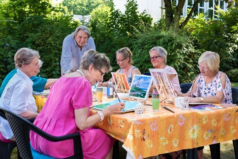 采取艺术教训坐户外在桌上和绘画,跟随的男性辅导员的资深夫人 免版税图库摄影