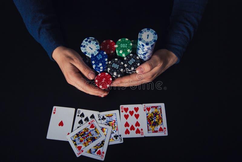 采取芯片的打牌者对他的银行,赢得在有赌博娱乐场的赌桌上同花大顺卡片组合 ?? 库存图片