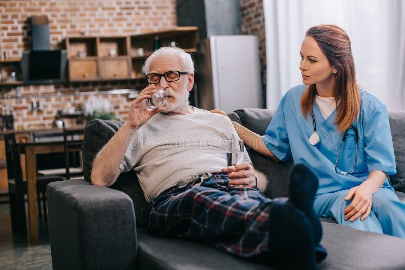采取药片和护士坐的老人 免版税库存图片