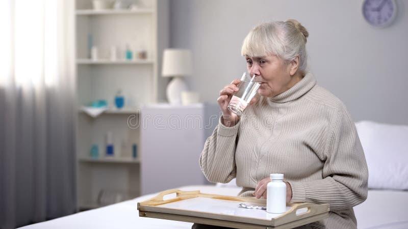 采取药片和饮用水在康复中心,医疗保健的资深夫人 库存照片