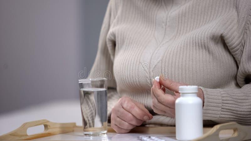 采取药片的年迈的妇女,遭受无可救药的疾病,康复中心 库存照片