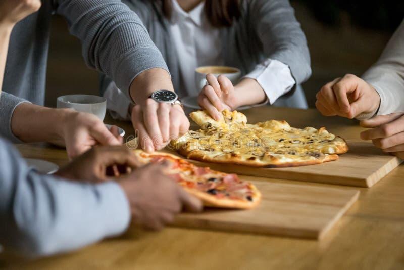 采取薄饼的不同的人民的手在比萨店切用餐 库存照片