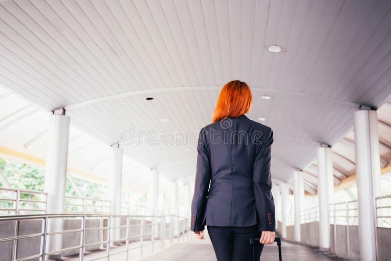 采取行李和走向平台方式的女实业家 库存照片