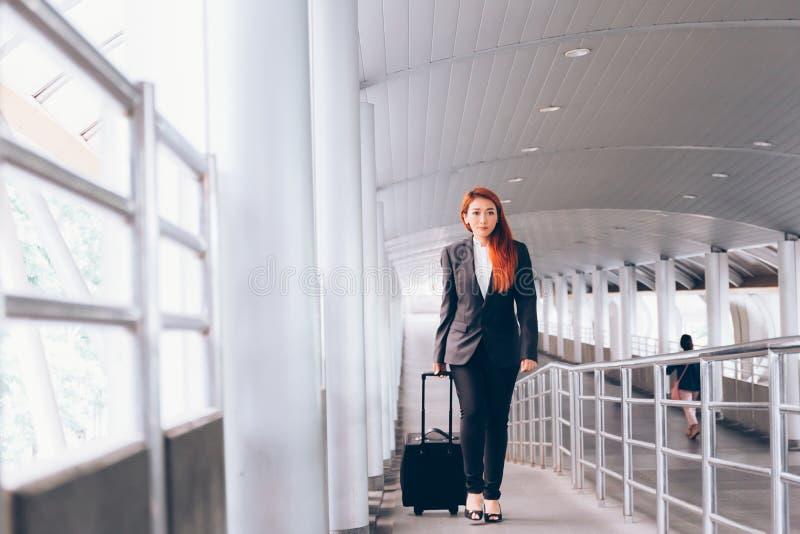 采取行李和走向平台方式-商务旅游的亚裔女实业家和通勤人概念 免版税库存图片