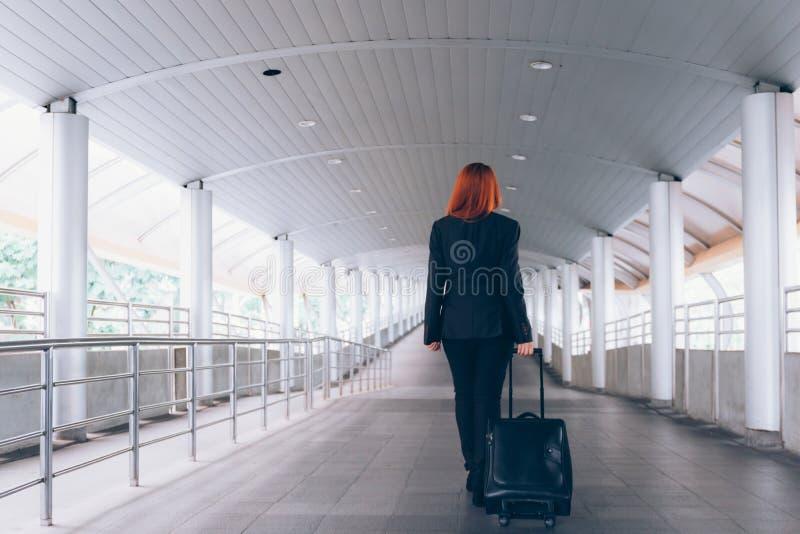 采取行李和走向平台方式-商务旅游的女实业家和通勤人概念 库存图片