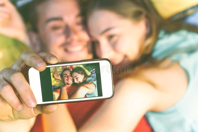 采取说谎在草的恋人年轻夫妇采取与手机的一selfie 免版税库存图片