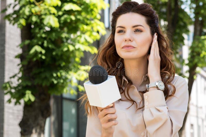采取采访的美丽的严肃的女性新闻广播员 库存图片